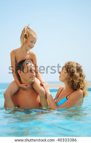 happy family in pool. Daughter sits on fathers shoulder