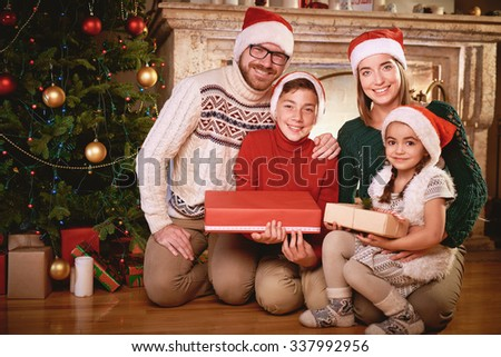 Happy family in Santa caps looking at camera by Christmas tree - stock photo