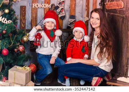 Happy family in Santa's costumes near Xmas tree excited - stock photo