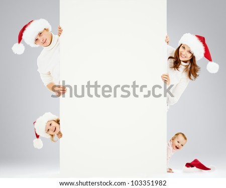 Happy family in Santa's hats. It is good for Christmas advertisement. - stock photo