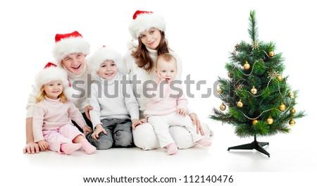 happy family in Santa's hats near christmas tree isolated on white - stock photo