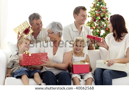 Happy family in sofa giving presents for Christmas - stock photo