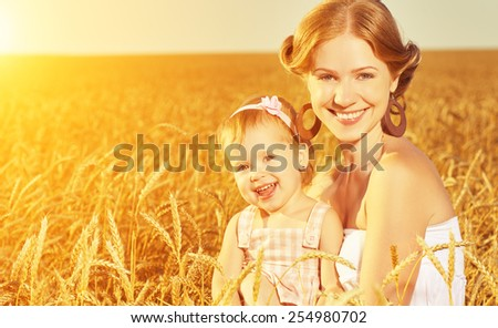 happy family in summer nature. Mother and baby daughter laugh, hug, play in the wheat field - stock photo