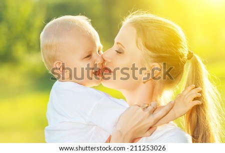 happy family in summer nature. mother kissing her baby - stock photo