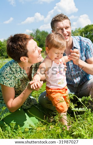 Happy family in the green sunny meadow