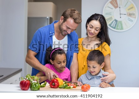 Happy family in the kitchen chopping vegetables at home - stock photo