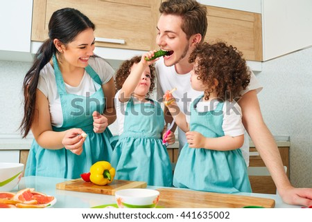 Happy family in the kitchen. Mom, dad, twin daughters playing and having fun in the kitchen preparing. My daughter feeds dad cucumber, another daughter and her mother with a smile face.  - stock photo