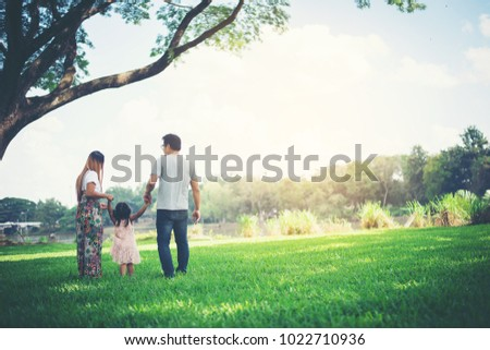 Happy family in the park, Father and Mother playing with daughter, relax family time