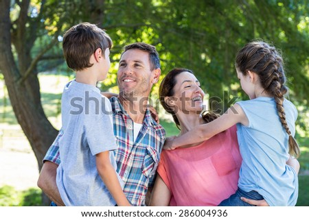 Happy family in the park together on a sunny day - stock photo