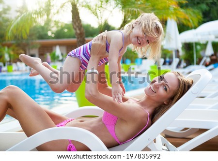 Happy family in the pool, having fun, mother with baby, summer holidays, vacation concept - stock photo