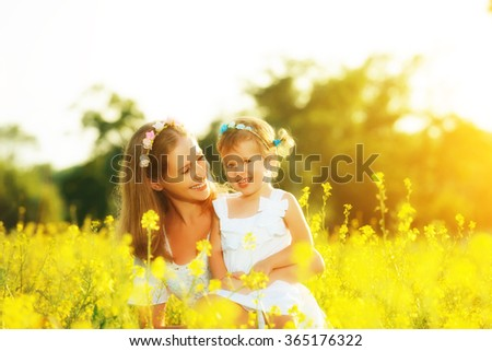 happy family in the summer meadow, mother embrace little daughter girl child with yellow flowers - stock photo