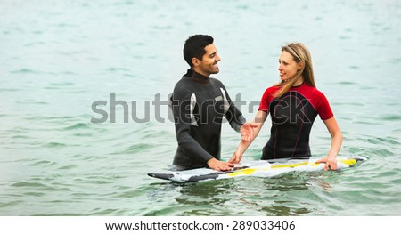 Happy family in the water with surf board  - stock photo