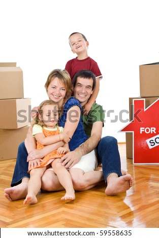 Happy family in their new home sitting on the floor with cardboard boxes - isolated