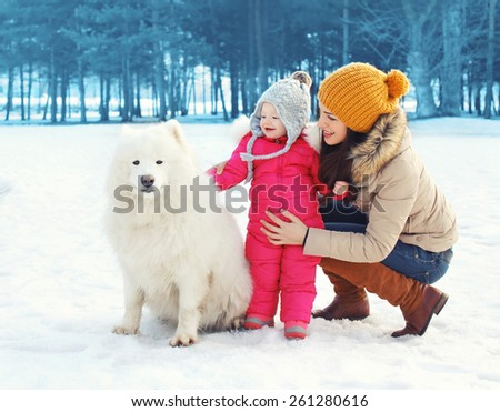 Happy family in winter day, mother and child walking with white Samoyed dog in the park - stock photo
