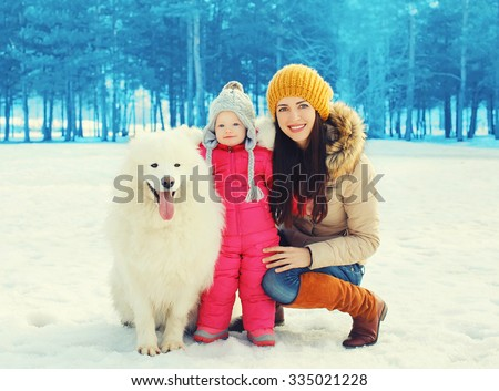 Happy family in winter day, smiling mother and child walking with white Samoyed dog in park