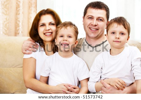 happy family indoor; shallow DOF, focus on mother eyes - stock photo