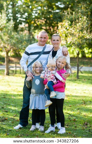 Happy family is posing in front of the camera in the park in sunny weather. - stock photo
