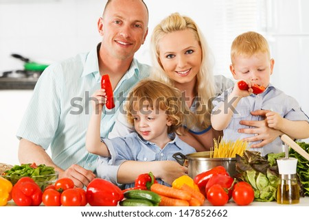 Happy family is preparing a healthy dinner in the kitchen.