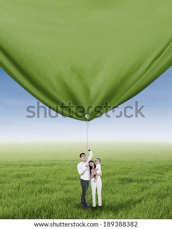 Happy family is pulling big banner on the meadow - stock photo