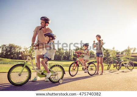 Happy family is riding bikes outdoors and smiling. Parents are teaching their children. Mom is holding fists