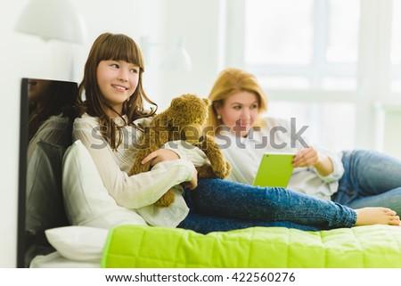 happy family. joyful and dreaming daughter holding teddy bear lies beside mom - stock photo
