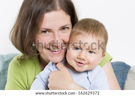 Happy family: Joyful mother embracing her cute smiling baby boy with affection. - stock photo