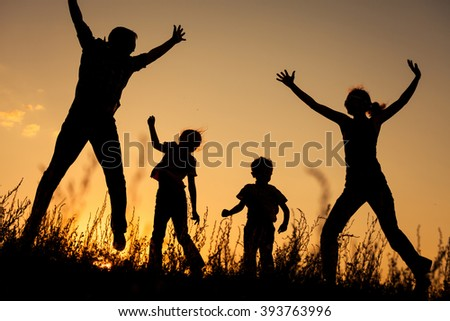 Happy family jumping in the park at the sunset time. Concept of friendly family.