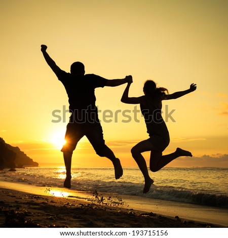 Happy family jumping on the beach at the dawn time - stock photo