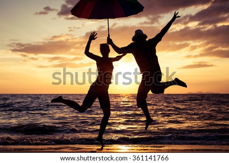 Happy family jumping on the beach at the sunset time.. Concept of friendly family. - stock photo