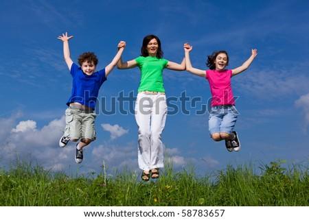 Happy family jumping outdoor - stock photo