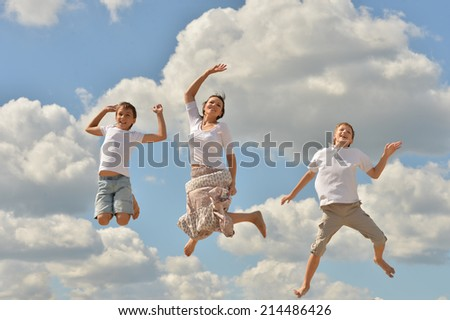 Happy family jumping over blue cloudy summer sky
