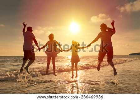 happy family jumping together on the beach - stock photo