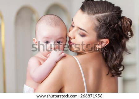Happy family laughing faces, mother holding adorable child baby boy, smiling and hugging - stock photo