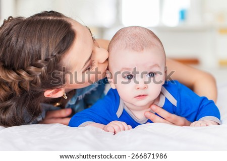 Happy family laughing faces, mother holding adorable child baby boy, smiling and hugging
