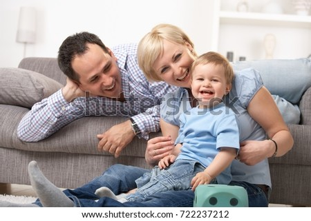 Happy family laughing together, baby looking at camera.