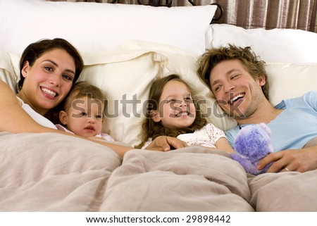 Happy family laying in bed - stock photo