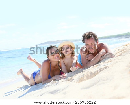 Happy family laying on a sandy beach - stock photo