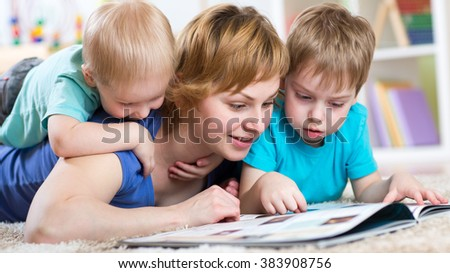 happy family lie on the floor and reading a book - stock photo