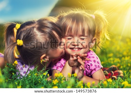 happy family. little girls twin sisters kissing and laughing in the summer outdoors - stock photo