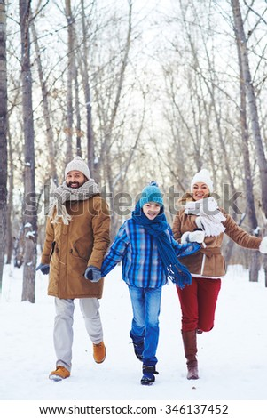 Happy family looking at camera while walking in winter park - stock photo