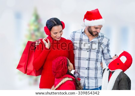Happy family looking at each other against blurry christmas tree in room - stock photo