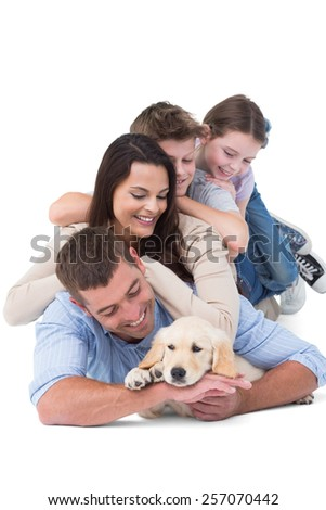 Happy family looking at puppy while lying on top of each other over white background - stock photo