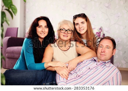 Happy family looking at the camera. Family at home relaxing on carpet. Indoors, lifestyle - stock photo