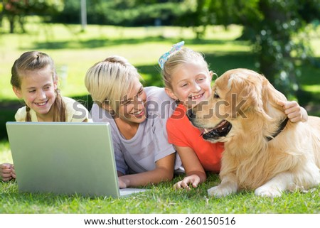Happy family looking at their dog on a sunny day - stock photo