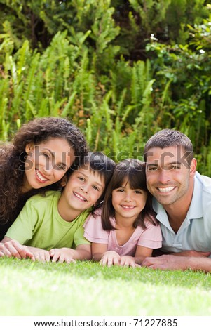 Happy family lying down in the garden - stock photo