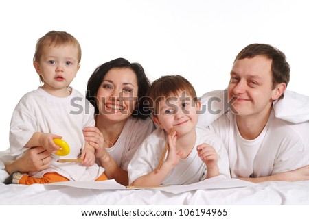 Happy family lying in bed on a white background