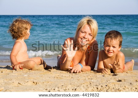 Happy family lying in the sand by the sea - stock photo