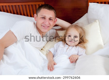 Happy family lying on a bed - stock photo