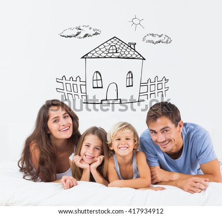 Happy family lying on a bed against hand drawn house
