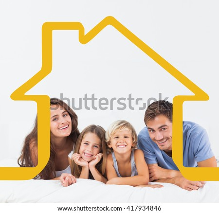 Happy family lying on a bed against house outline